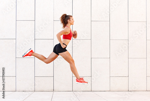 Concept of sporting success. strong girl runs and jumps high against the background of the city wall.