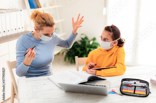 Fototapeta Child home studying education, homeschooling, with private tutor / mother with protective mask in the time of viruses, flu and seasonal pandemic, healthy approach in social contact. obraz