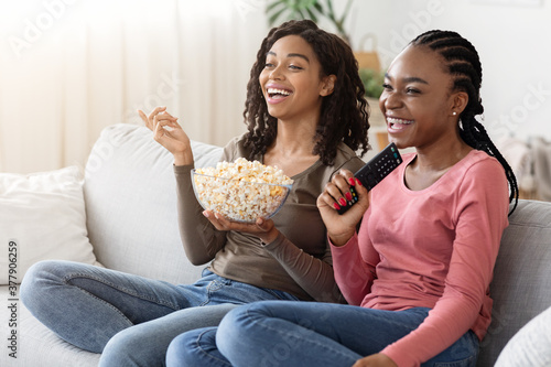 Fotografija Happy african girlfriends eating popcorn and watching movie