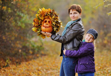 Mother And Little Daughter On The Background Of The Autumn Forest Smiling Hugging And Holding A Pumpkin-Jack's Lantern - A Symbol Of The Halloween Holiday.