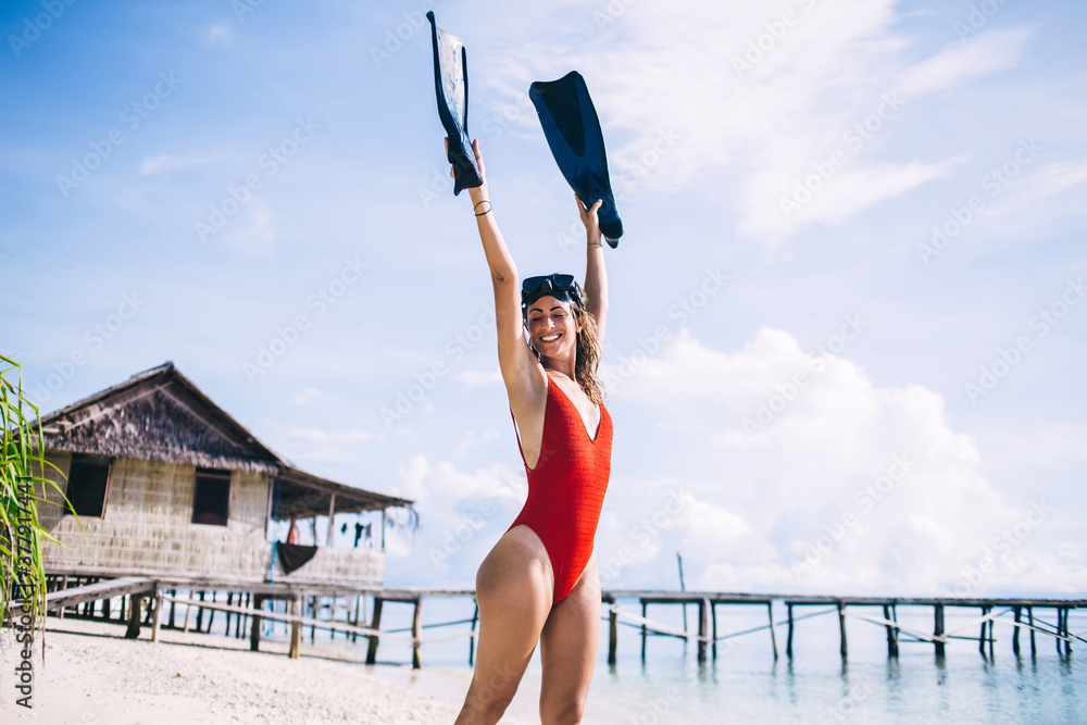 Fototapeta Joyful woman raising swim flippers while satisfy at sea coastline of tropical island on Bahamas, happy female swimmer rejoicing during leisure time for practicing snorkeling hobby on Raja Ampat