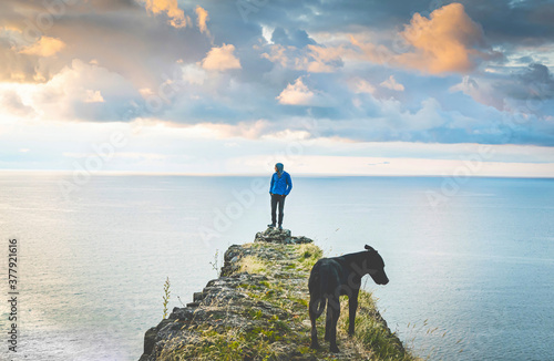 Valokuva Person with a dog stands on the edge and looks to the sides with sea and dramatic sky in the backgrond