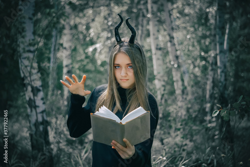 Foto Beautiful young girl with brown hair in a witch costume, conjuring over a book, against the background of a dark forest