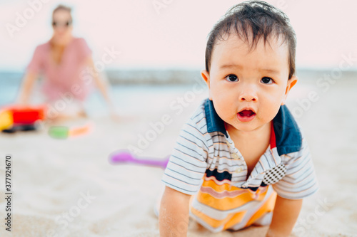Fototapeta Baby boy playing with beach toys with his mother on tropical beach