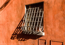 Old Iron Grating Window On A Red Plaster Wall In Typical Italian Alley