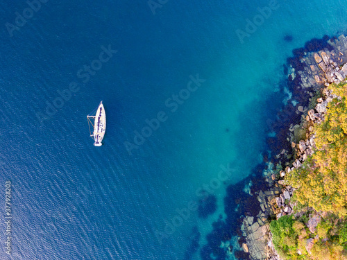 Canvas Print Aerial drone bird's eye view of one sailboat yacht anchored at Store Beach near Quarantine Station in Manly, the beachside suburb of Sydney, New South Wales, Australia, in the evening before sunset