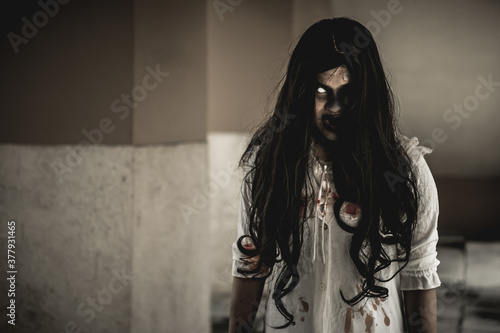 Fototapeta Woman in ghost or zombie on halloween festival at dark place, holding knife and wants to stab you