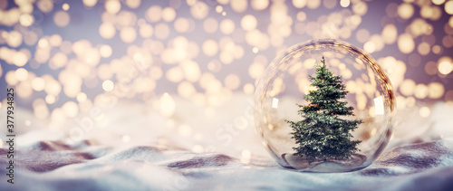 Fotografia Christmas tree in glass ball on snow. Glitter lights