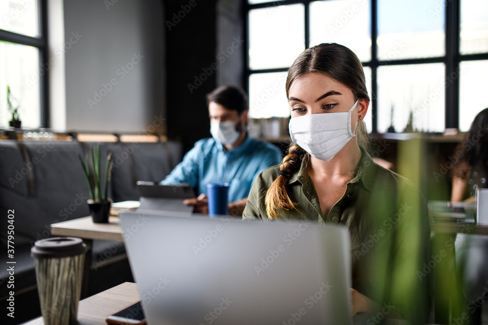 Fototapeta Business people with face masks indoors in office, back to work after coronavirus lockdown.
