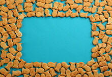 Frame Of Delicious Goldfish Crackers On Blue Background, Flat Lay. Space For Text