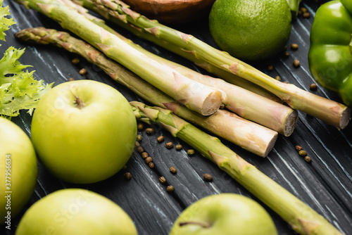 Fotografia fresh green ripe apples and asparagus on wooden surface
