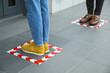Leinwandbild Motiv People standing on taped floor markings for social distance, closeup. Coronavirus pandemic