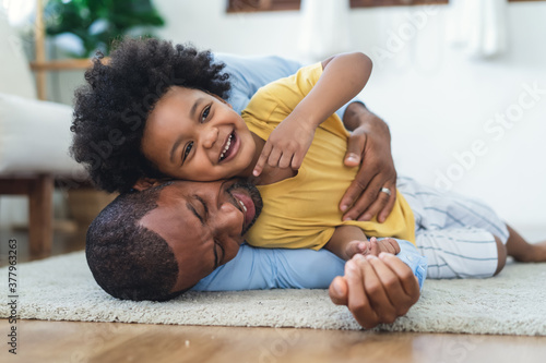 Black father in living room have a fun playing together on warm floor at home Fotobehang