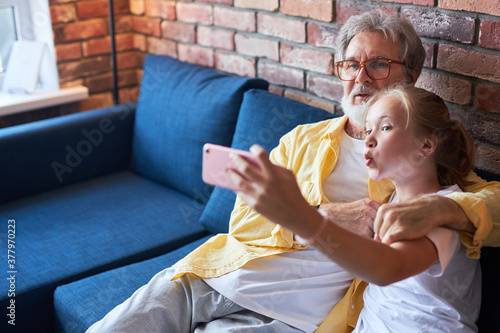 Cuadros en Lienzo modern grandfather having fun with granddaughter, they take photo on smartphone