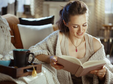 Happy Woman Reading Book At Modern Home In Sunny Autumn Day