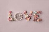 Newborn love background - word Love spelled with flowers and round bowl on light pink background