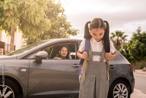 Photo Young mother leaves her daughter at school with the car