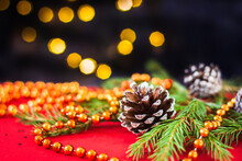 Christmas New Year's Composition. A Pine Cone Lies On A Red Background With Orange Christmas Beads, Behind A Bokeh On A Dark Background