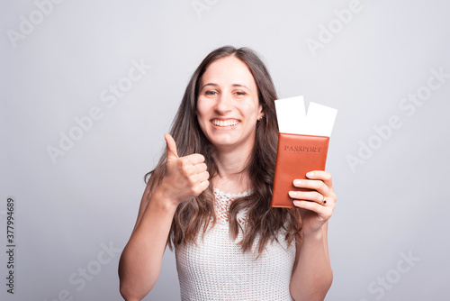 Portrait of happy woman showing thumb up and passport with flight tickets Fotobehang