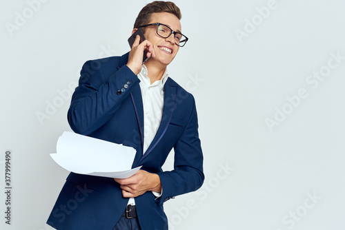 Fotografía Business man in a suit talking on the phone with glasses with documents technolo