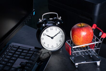 Online Shopping Concept Modern Background With Red Apple In Shopping Cart, Alarm Clock And Computer Keyboard On Black Table. Online Store, Sale Business Concept And Consumer Society Trend.