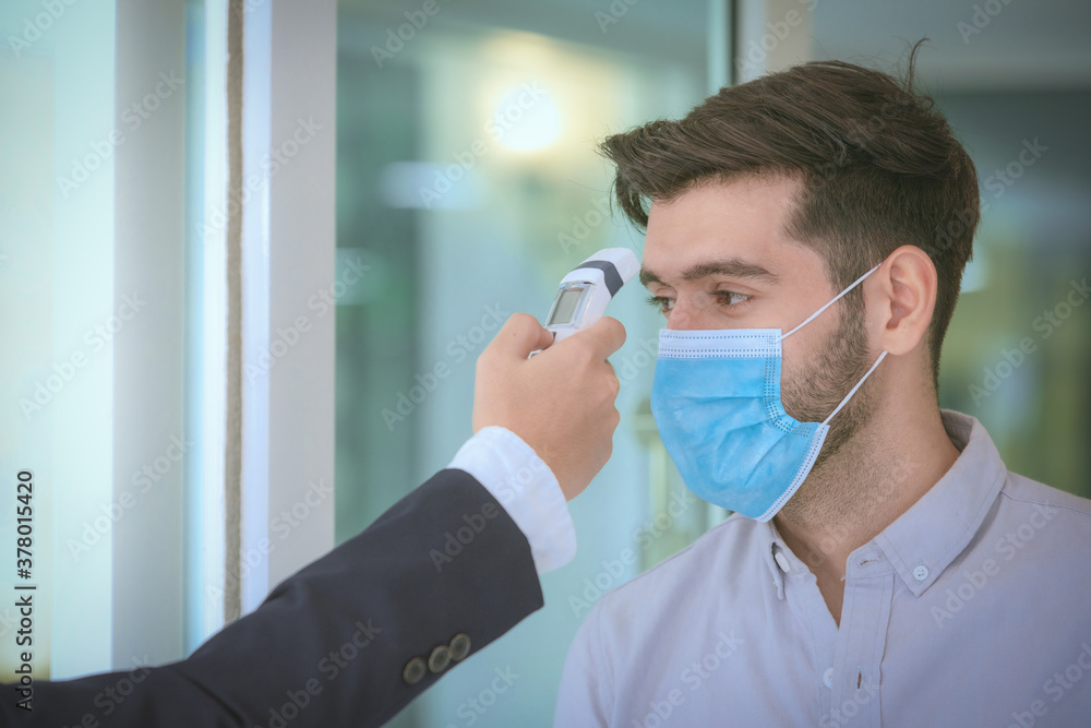 Fototapeta Body temperature check,Receptionist and guest wearing face mask at front desk while having conversation at hotel.Covid 19 and coronavirus infection protection and protective policy concept .