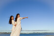 夕暮れの海を指差す二人の女性