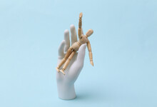 White Mannequin Hand Holds Wooden Puppet On Blue Background