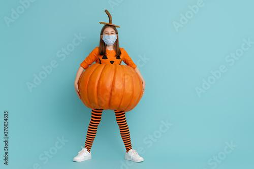girl in pumpkin costume  wearing face mask Billede på lærred