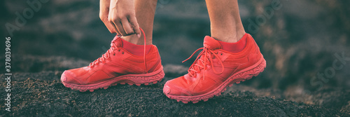 Fototapeta Walking woman tying shoe laces getting ready to walk or run lacing red running shoes banner. Panoramic crop of active person going outside. obraz