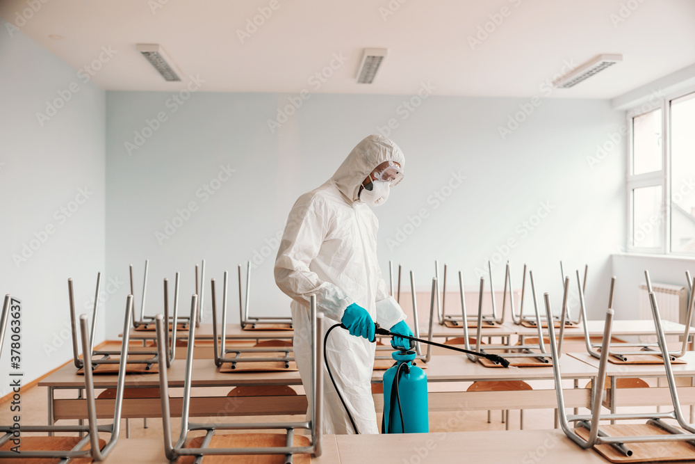 Fototapeta Man in sterile uniform, with gloves and mask holding sprayer and spraying with disinfectant desks and chairs in classroom.