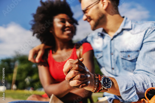 Closeup of young smiling multicultural hipster couple holding hands and sitting outdoors on a beautiful sunny day Canvas Print