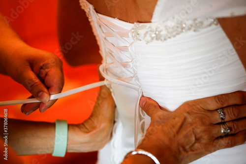 Photo dressing the bride, lacing the bodice dress