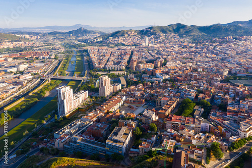 Fototapeta Aerial urban landscape of Santa Coloma de Gramenet municipality and Besos river, Catalonia, Spain obraz