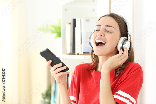 Obraz na plátně Happy teen singing listening to music on phone at home