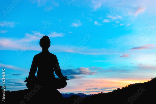 Silhouette human practicing yoga on mountain at sunset Fotobehang