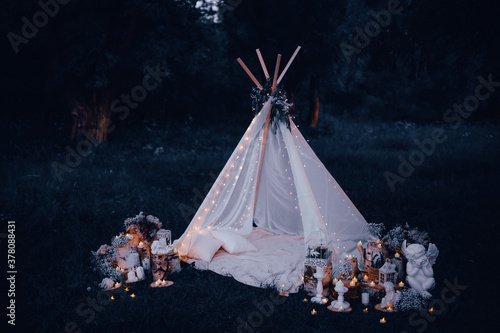 Obraz white air tent for a romantic evening. wedding night decor, candles, angel - fototapety do salonu