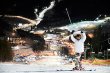 Full Length Of Male Skier In Winter Ski Jacket And Helmet Raising Ski Poles And Looking At Camera. Young Man In Ski Goggles Standing On Snow-covered Slope With Beautiful Night City On Background