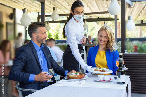 Fototapeta Handsome couple having lunch in the restaurant, being served by waitress with a mask, corona time obraz
