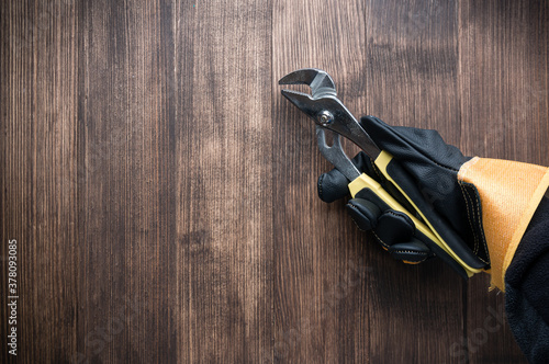 worker's gloved hand holds a pliers tool on a wooden background Canvas Print