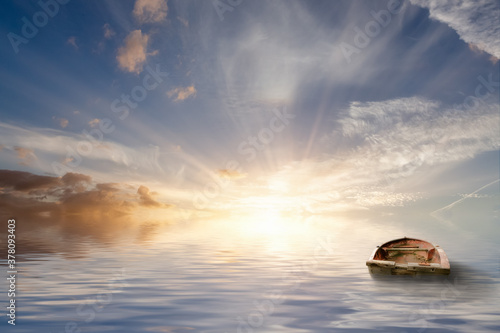 Old rowing boat adrift at sea