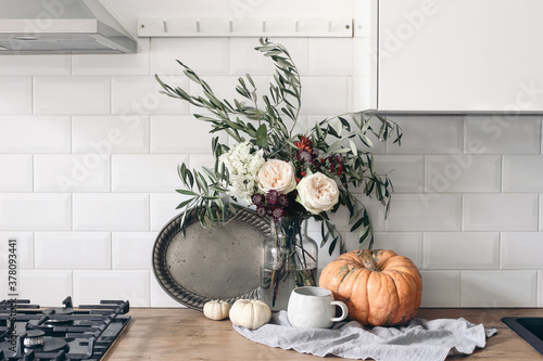 Fototapeta Autumn still life composition in rustic eclectic kitchen interior. Cup of coffee, vintage silver tray and floral bouquet. Wooden table background with pumkins. Thanksgiving, Halloween concept. obraz