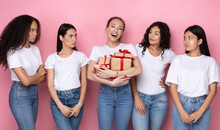 Envious Women Looking At Friend With Many Gifts, Pink Background