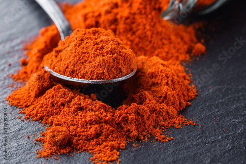 Fotografiet aromatic ground paprika on a dark stone background