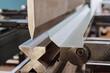 Leinwandbild Motiv Bending sheet metal with a hydraulic machine at the factory