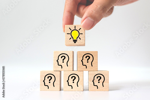 Concept creative idea and innovation. Hand picked wooden cube block with light bulb icon on top pyramid and head human symbol - 378103068