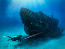 A Scuba Diver With A Torch Explores A Sunken Shipwreck At The Seabed Of The Maldives Islands, Indina Ocean