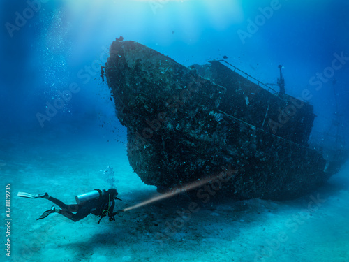 Fotografía A scuba diver with a torch explores a sunken shipwreck at the seabed of the Mald