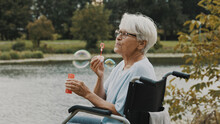 Senior Gray Haired Disabled Woman In The Wheelchair Blowing Soap Bubbles Near The River. High Quality Photo