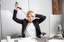 Totally Depressed Young Employee At Work With Tangled Telephone Cable Around Her Neck